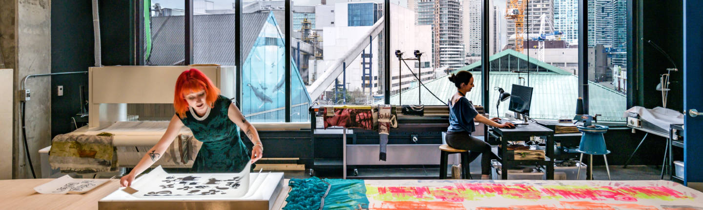 Artist laying out prints and garments with another working on a computer