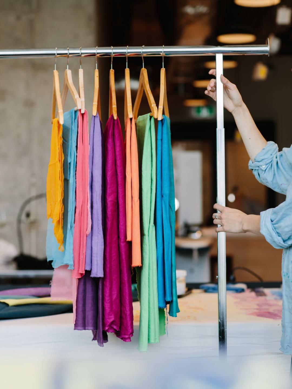 Person pulling garment rack full of colourful fabrics