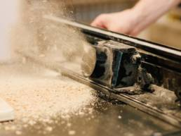 Sawdust flying out from automated sawing machine