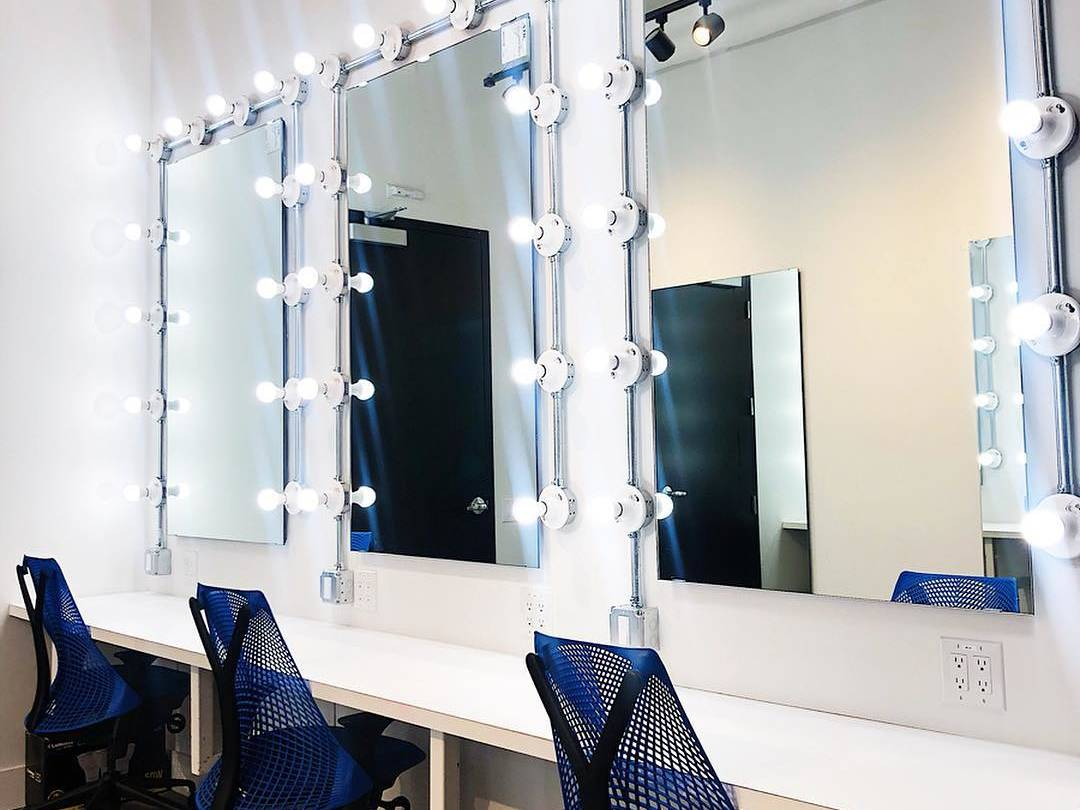 3 large vanity mirrors with 3 blue chairs tucked in front