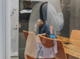 Person on phone sitting down at meeting table through glass window