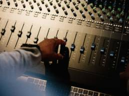 Hand pushing up fader switch on sound mixing console